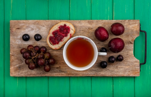 Top view of breakfast set with bread slice smeared with raspberry jam grape cup of tea and pluots with sloe berries on cutting board on green background