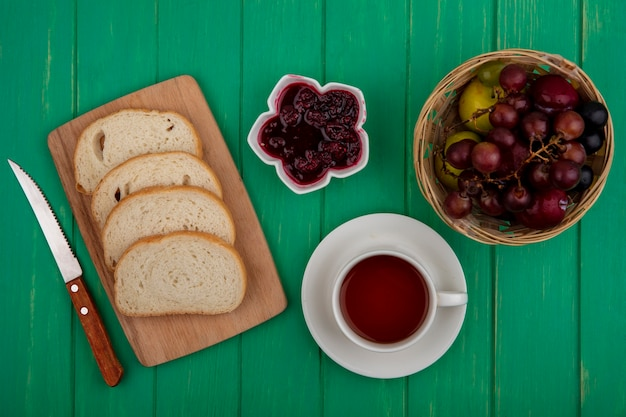 Top view of breakfast set with bread slices on cutting board raspberry jam and cup of tea with pluot and grape in basket and knife on green background