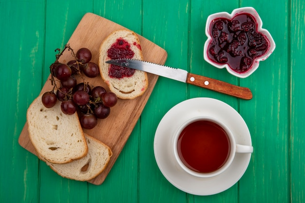 Top view of breakfast set with bread slices and grape with knife and cup of tea with bowl of raspberry jam on green background