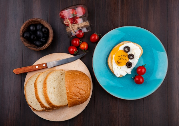 Top view of breakfast set with bread slices and knife on cutting board and plate of fried egg with tomatoes spilling out of bowl and bowl of black olive on wood