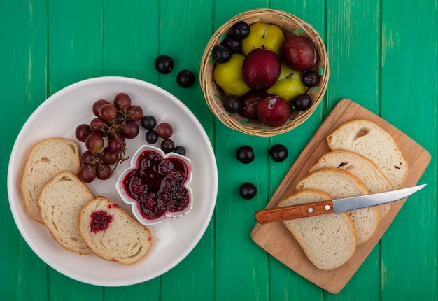 Top view of breakfast set with bread slices raspberry jam and grape in plate and bread slices with knife on cutting board with basket of pluots on green background