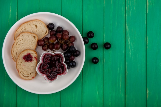 Top view of breakfast set with bread slices raspberry jam and grape in plate on green background with copy space