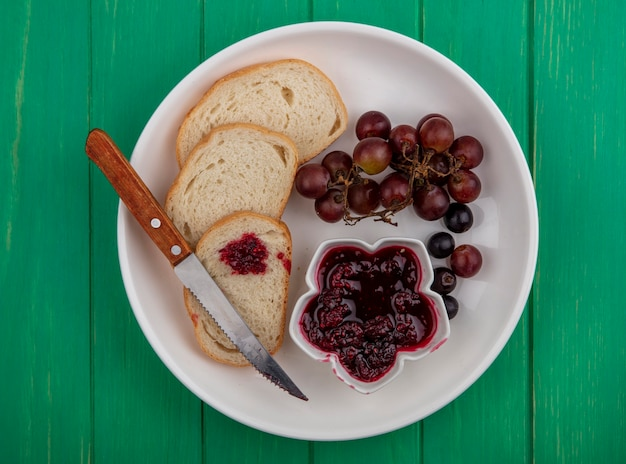 Top view of breakfast set with bread slices raspberry jam and grape with knife in plate on green background
