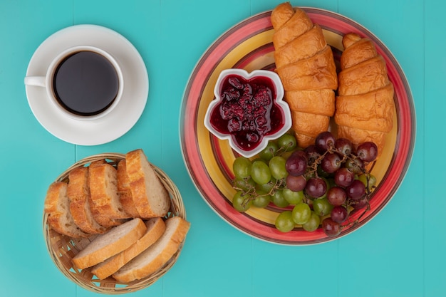 Top view of breakfast set with croissant grape raspberry jam and bread slices with cup of tea on blue background