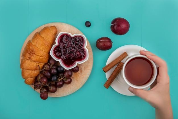 Vista dall'alto del set per la colazione con croissant e marmellata di lamponi uva sul tagliere e mano femminile che tiene tazza di tè con cannella e pluots su sfondo blu