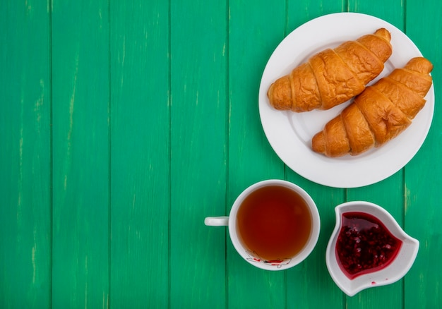 Top view of breakfast set with croissants in plate cup of tea raspberry jam in bowl on green background with copy space