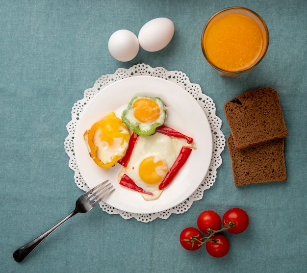 Top view of breakfast set with egg and pepper and orange juice black bread tomatoes on blue background with copy space