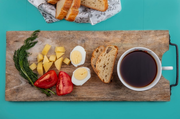 Top view of breakfast set with egg tomato potato and dill with cup of tea on cutting board and breads on blue background