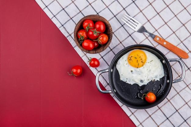 Vista dall'alto del set da colazione con padella di uovo fritto e ciotola di forchetta di pomodoro su panno plaid su rosso con spazio di copia