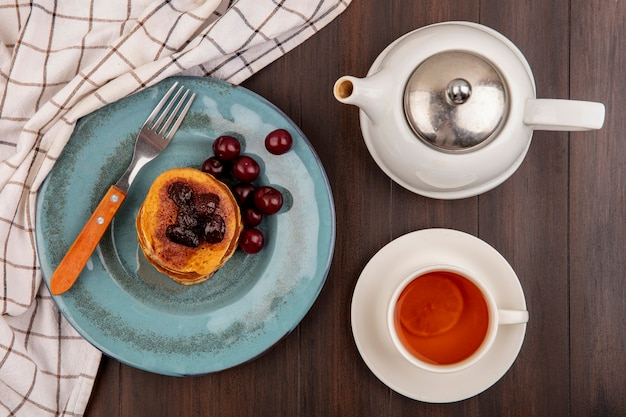 Top view of breakfast set with pancake and cherries and fork in plate on plaid cloth and cup of tea with teapot on wooden background