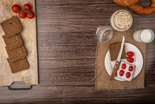 Top view of breakfast set with rye bread slices smeared with cottage cheese and tomatoes with milk and oat-flakes on wooden background with copy space