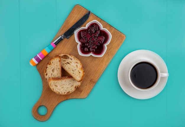 Top view of breakfast set with sliced baguette and raspberry jam with knife on cutting board and cup of tea on blue background