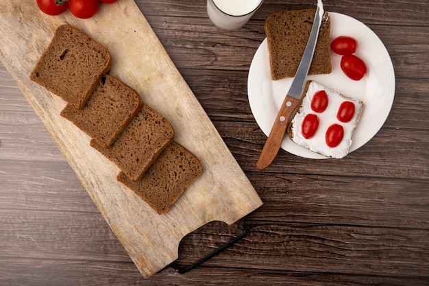 Top view of breakfast set with sliced rye bread smeared with cottage cheese and tomatoes with knife in plate on wooden background