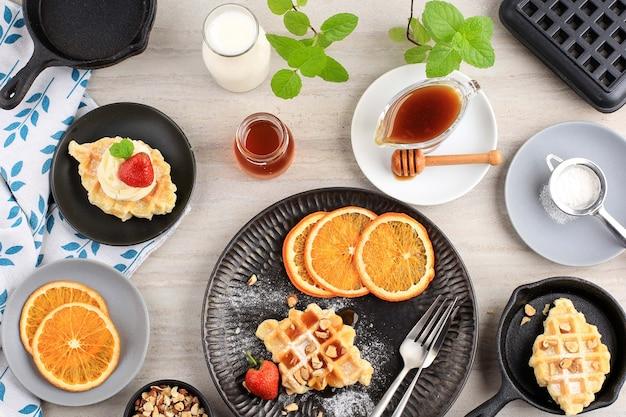 クロワッサンワッフルまたはクロワッフル、ストロベリー、スライスしたオレンジ、蜂蜜、メープルシロップのトップビュー朝食設定テーブル