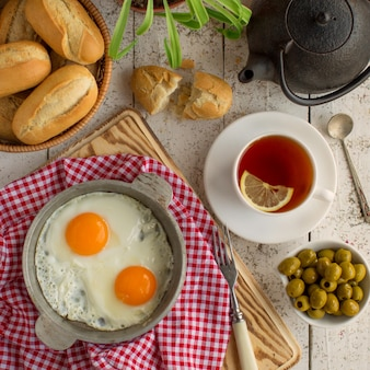 Top view of breakfast setup with eggs, olives, bread and black tea