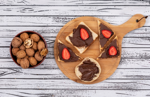 Top view of breakfast toasts with chocolate and strawberry on cutting board and walnuts in bowl on white wooden surface horizontal