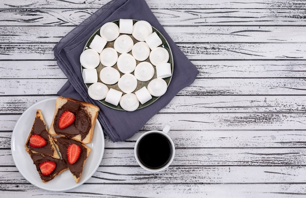 Top view of breakfast toasts with chocolate and strawberry, marshmallow and coffee on white wooden surface horizontal
