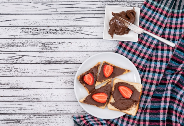 Top view of breakfast toasts with chocolate and strawberry with copy space on white wooden background horizontal