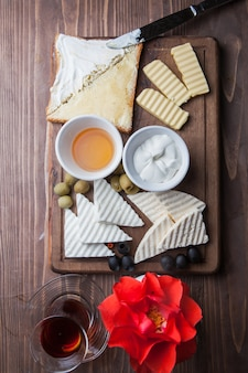 Top view breakfast with cheese and flower and glass of tea in board cookware