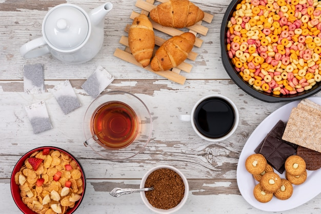 Top view of breakfast with cornflakes, croissants, coffee and tea on white wooden surface horizontal