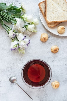 Top view of a breakfast with a cup of tea cookies bread and flowers