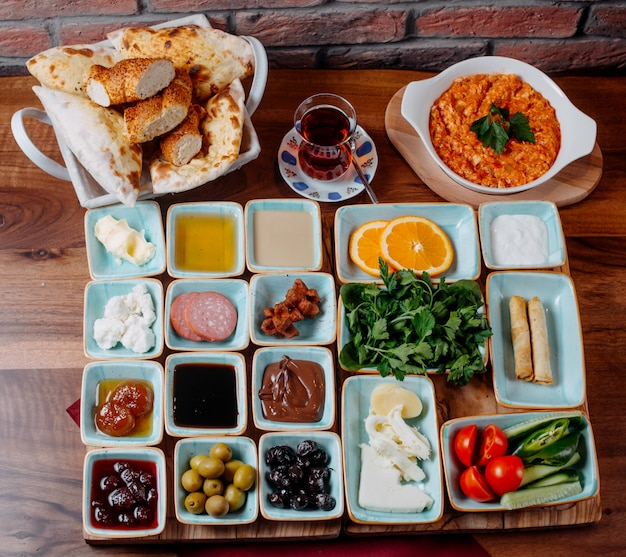 Top view of breakfast with fried eggs honey jams fresh vegetables and cheese on a wooden table
