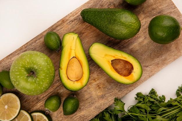 Vista dall'alto di avocado verde brillante su una tavola di cucina in legno con mele limette e feijoas su una superficie bianca