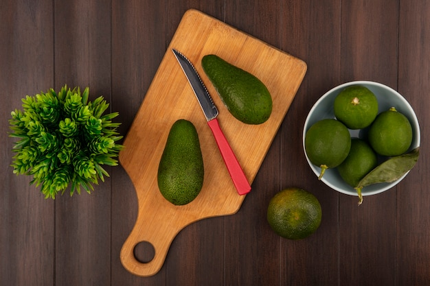 Top view of bright green avocados on a wooden kitchen board with knife with limes on a bowl with tangerine isolated on a wooden background