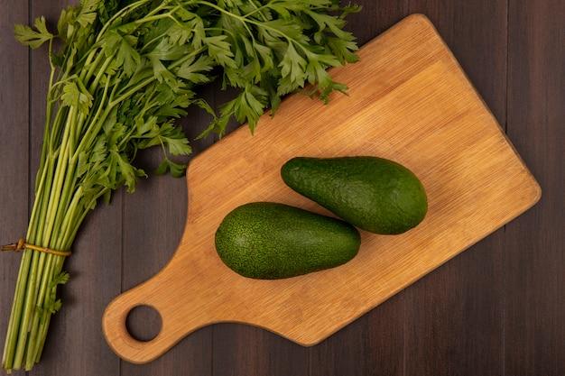 Vista dall'alto di avocado verde brillante su una tavola di cucina in legno con prezzemolo isolato su una parete in legno