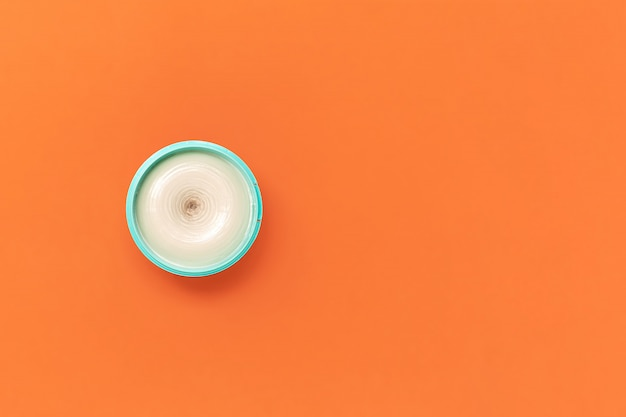 Top view on a bright jar of turquoise color with cosmetic cream on an orange . the concept of beauty, medicine, facial and body skin care, hair care