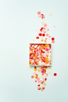 Top view of bright paper confetti in a box on pastel background.