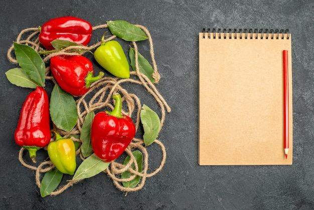 Top view bright peppers with laurel leaves next to notebook red pen on gray background with free space