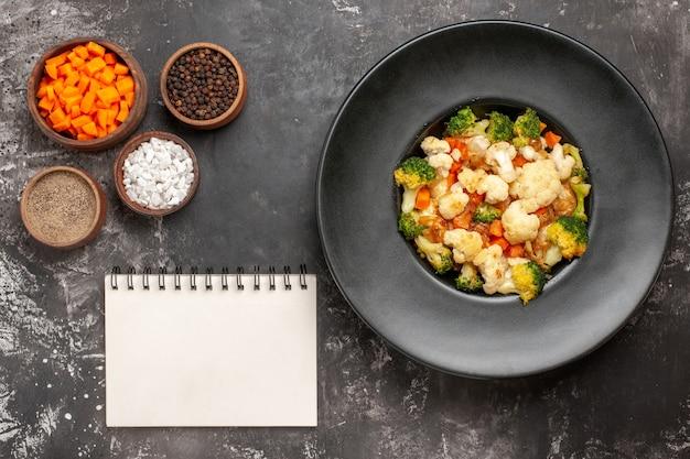 Вид сверху салат из брокколи и цветной капусты в черной миске, разные специи и нарезка моркови в мисках, блокнот на темной поверхности