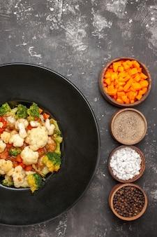 Вид сверху салат из брокколи и цветной капусты в черной миске, разные специи и нарезка моркови в мисках на свободном месте темной поверхности