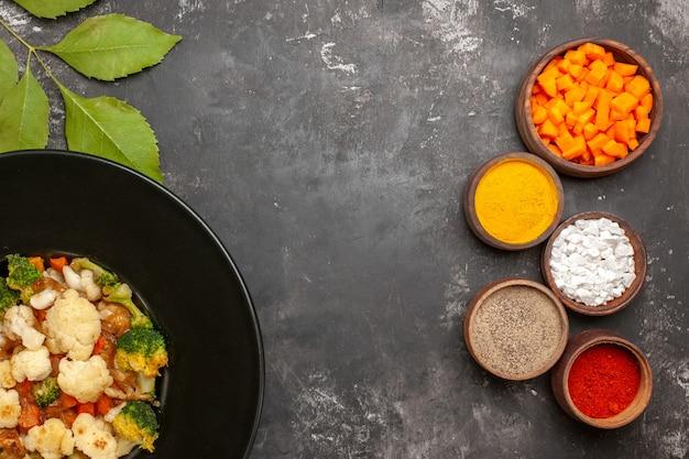 Вид сверху салат из брокколи и цветной капусты в черной миске, разные специи и нарезка моркови в мисках на темной поверхности с копировальным соком