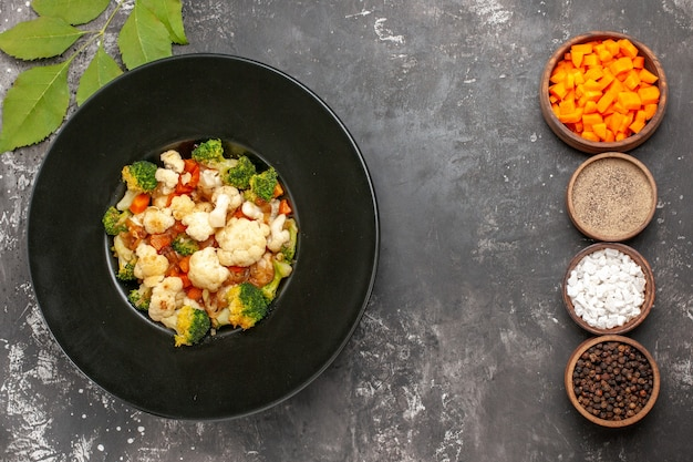 Вид сверху салат из брокколи и цветной капусты в черной миске, разные специи и нарезка моркови в мисках на темной поверхности