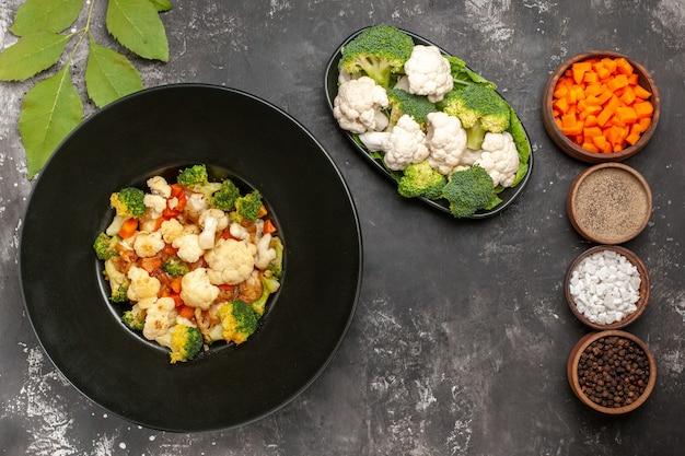 Вид сверху салат из брокколи и цветной капусты в черной миске, разные специи и нарезка моркови в мисках, сырая брокколи и цветная капуста на тарелке на темной поверхности