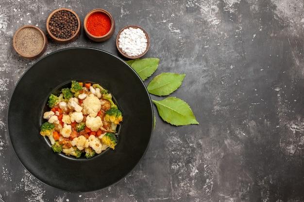 검은 그릇에 상위 뷰 브로콜리와 콜리 플라워 샐러드 그릇에 다른 향신료는 복사 sapce와 어두운 표면에 나뭇잎