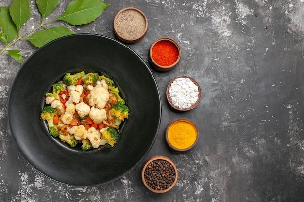 Вид сверху салат из брокколи и цветной капусты на черной овальной тарелке, разные специи в маленьких мисках на темной поверхности, свободном месте