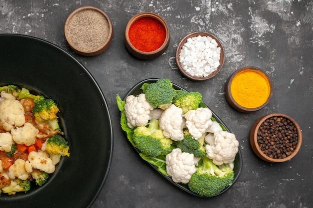 Вид сверху салат из брокколи и цветной капусты на черной овальной тарелке, разные специи в небольших мисках, сырая брокколи и цветная капуста на темной поверхности