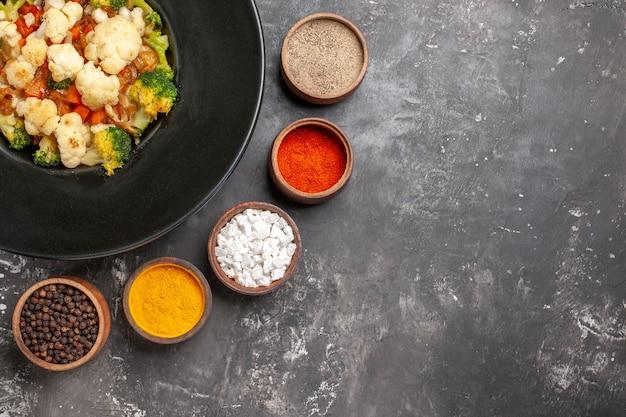 Вид сверху салат из брокколи и цветной капусты на черной овальной тарелке разные специи в небольших мисках куркума морская соль черный перец на темной поверхности свободное место