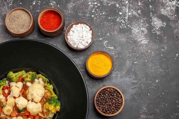 Вид сверху салат из брокколи и цветной капусты на черной овальной тарелке, разные специи в небольших мисках, куркума, морская соль, перец на темной поверхности, свободное место
