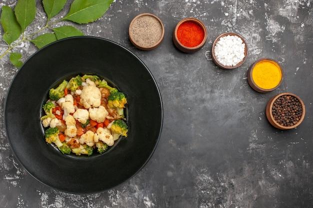 Вид сверху салат из брокколи и цветной капусты на черной овальной тарелке, разные специи в небольших мисках, куркума, морская соль, перец на темной поверхности