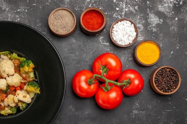 Вид сверху салат из брокколи и цветной капусты на черной овальной тарелке, помидоры с разными специями на темной поверхности