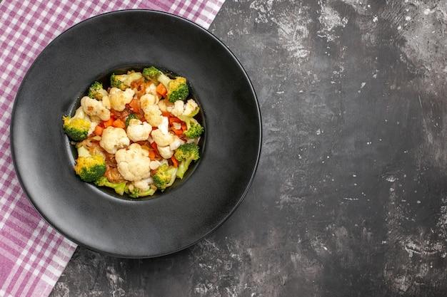 Вид сверху салат из брокколи и цветной капусты на черной тарелке, розово-белая клетчатая скатерть на темной поверхности, свободное пространство
