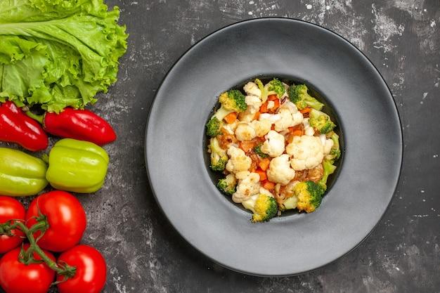 어두운 표면에 상위 뷰 브로콜리와 콜리 플라워 샐러드 토마토 녹색과 빨간색 피망 양상추