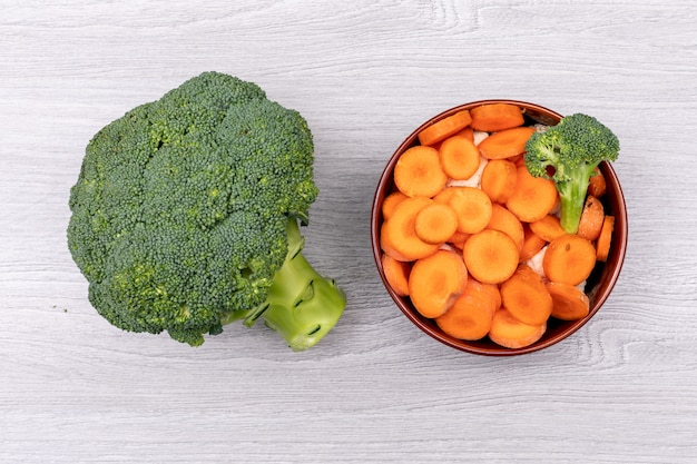 Top view broccoli and carrot in brown ceramic bowl on white surface