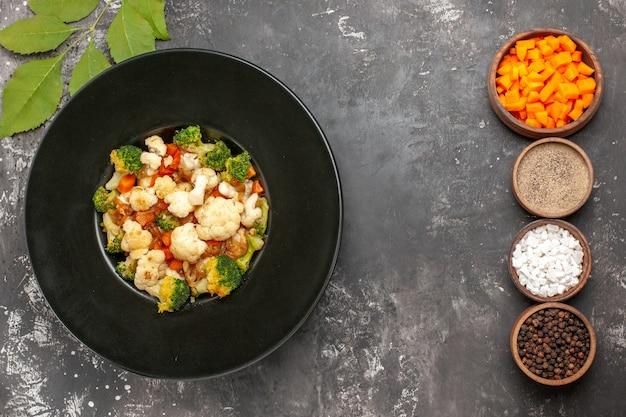 Vista dall'alto di broccoli e insalata di cavolfiore in ciotola nera diverse spezie e taglio di carote in ciotole sulla superficie scura