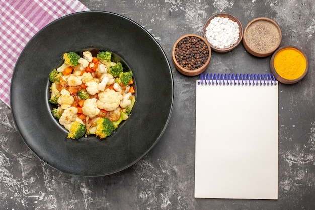 Top view broccoli and cauliflower salad in black bowl pink and white checkered napkin different spices a notebook on dark surface