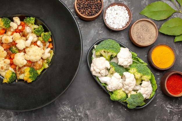 Top view broccoli and cauliflower salad in black bowl raw broccoli and cauliflower on plate different spices on dark surface